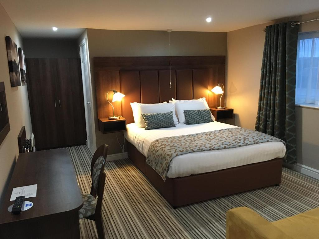 A bed or beds in a room at Twin Oaks Hotel