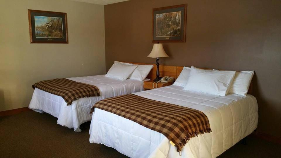 A bed or beds in a room at Spillover Motel and Inn