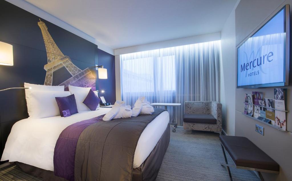 سرير أو أسرّة في غرفة في ميركيور باريس سنتر برج إيفل