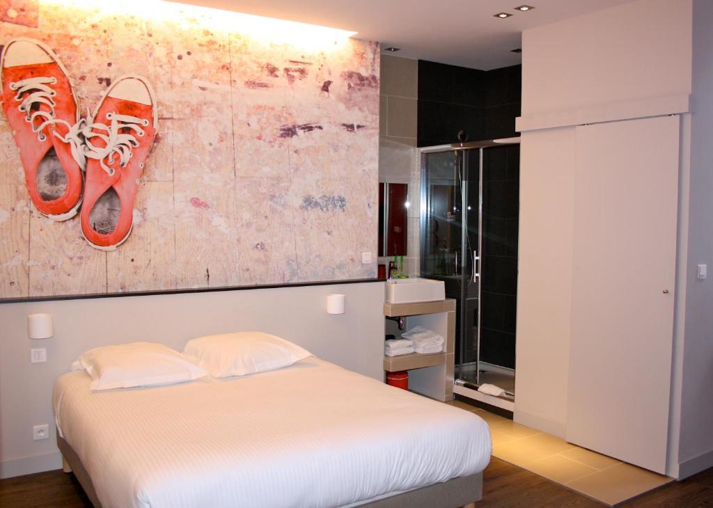 سرير أو أسرّة في غرفة في Hotel de la Presse Bordeaux Centre