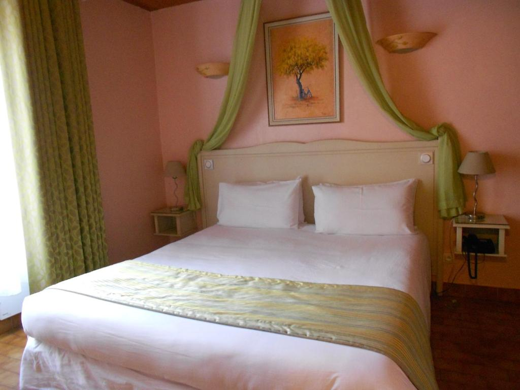 A bed or beds in a room at Hôtel Le Médiéval