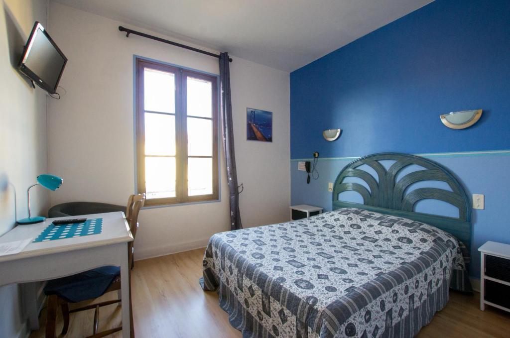A bed or beds in a room at Hôtel du Commerce