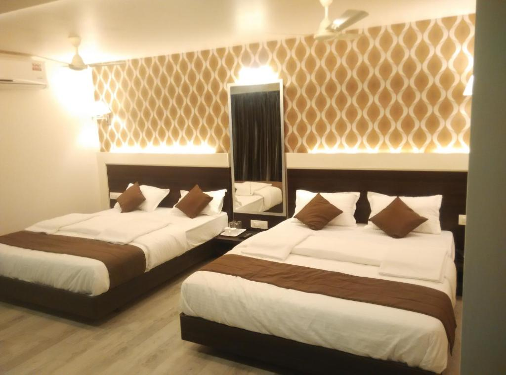 A bed or beds in a room at Hotel Sai Residency