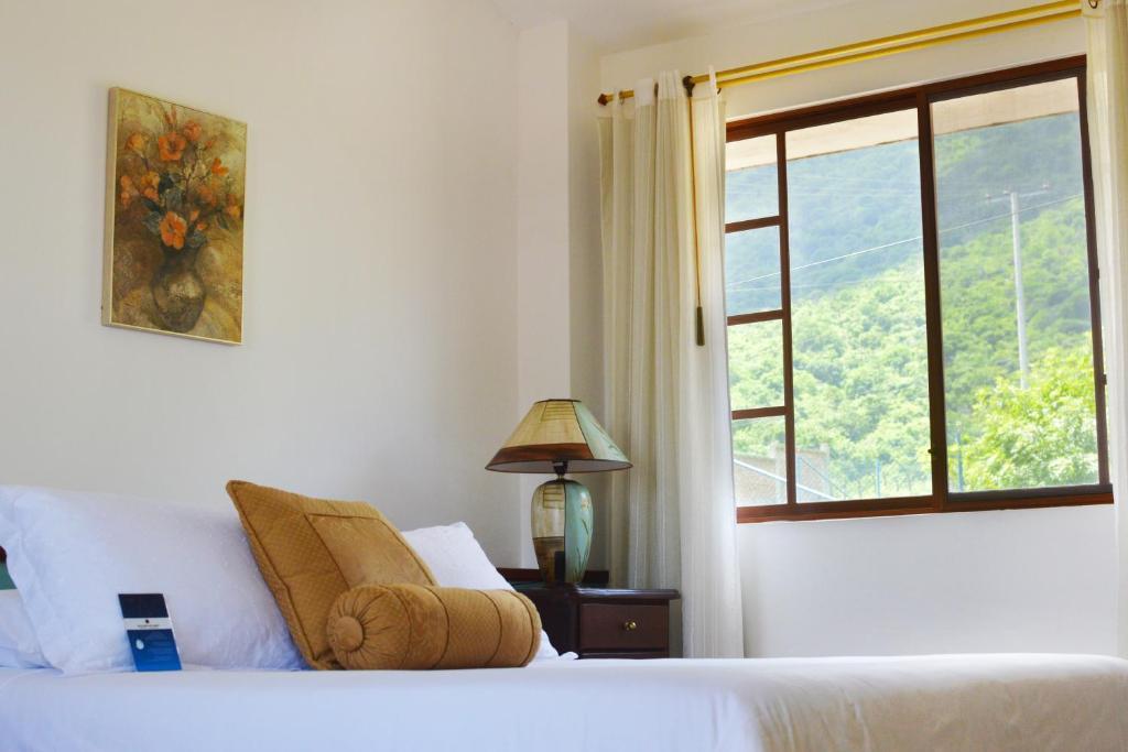 A bed or beds in a room at Balcones del Cerro Hotel - Cabañas