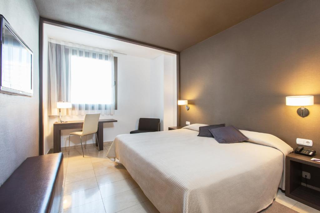 A bed or beds in a room at Expo Hotel Valencia