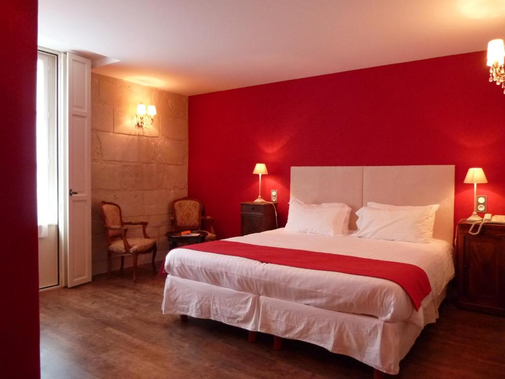 A bed or beds in a room at Hôtel Grand Monarque