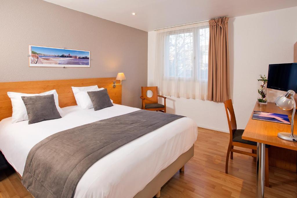 Ein Bett oder Betten in einem Zimmer der Unterkunft Séjours & Affaires Toulouse de Brienne