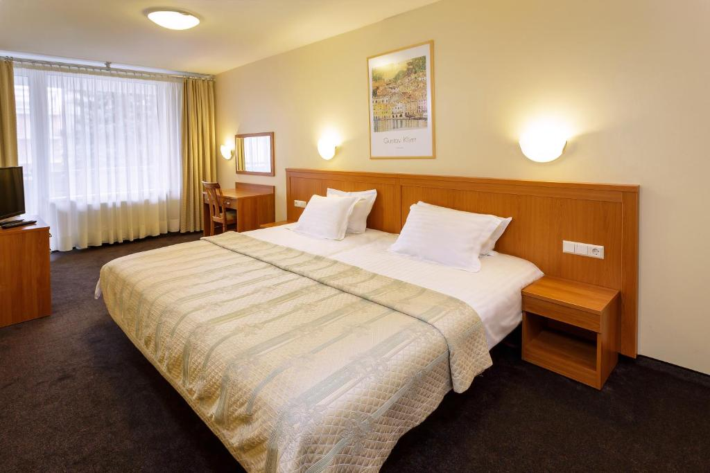 A bed or beds in a room at Alka Hotel