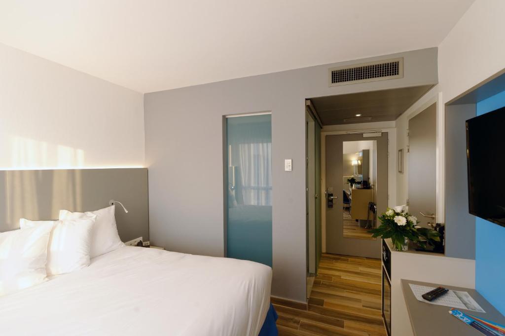 Ein Bett oder Betten in einem Zimmer der Unterkunft Colmar Hotel