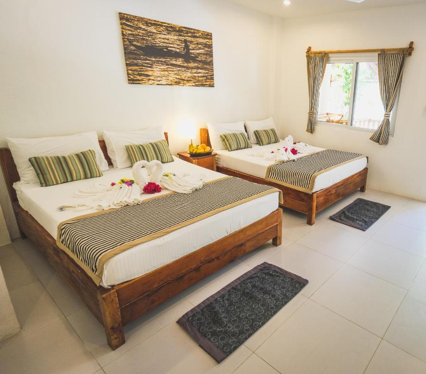 A bed or beds in a room at Evolution Dive and Beach Resort