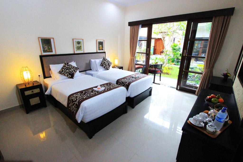 A bed or beds in a room at Gatra Ubud Inn