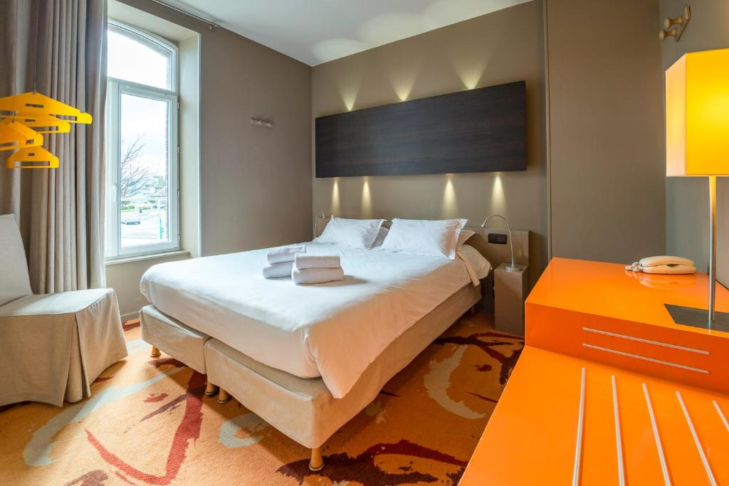 A bed or beds in a room at Hotel Aubade