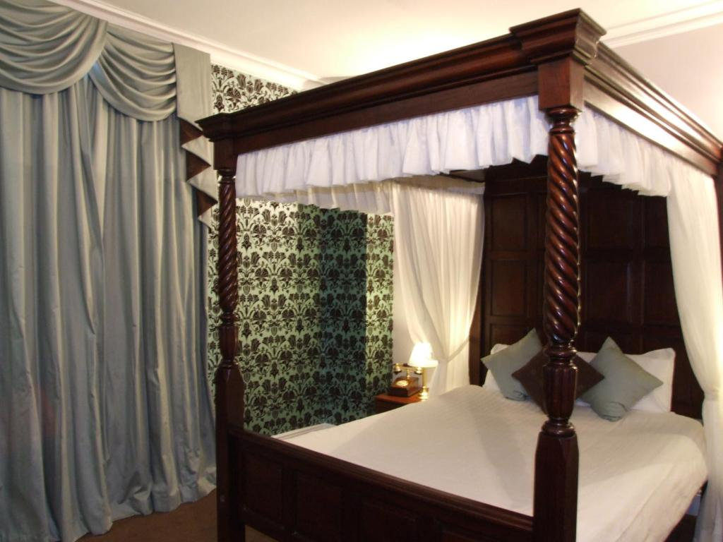 A bed or beds in a room at Ely House Hotel