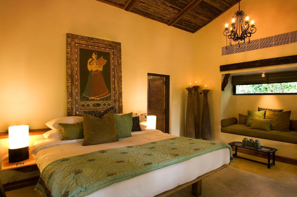 A bed or beds in a room at Baghvan Pench National Park - A Taj Safari Lodge