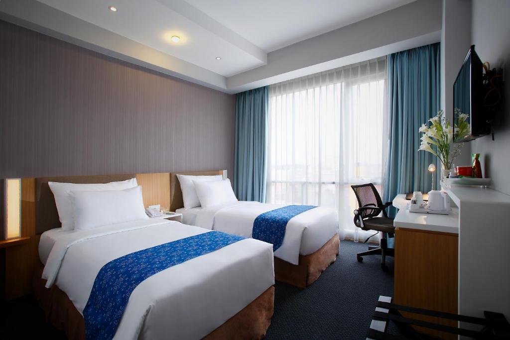 A bed or beds in a room at Hotel Grandhika Setiabudi Medan
