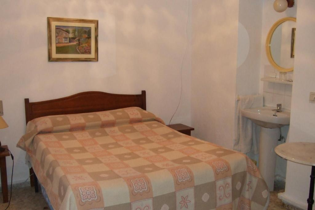 A bed or beds in a room at Hostal Alcázar