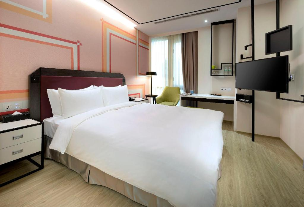 A bed or beds in a room at Uinn Business Hotel-Shihlin