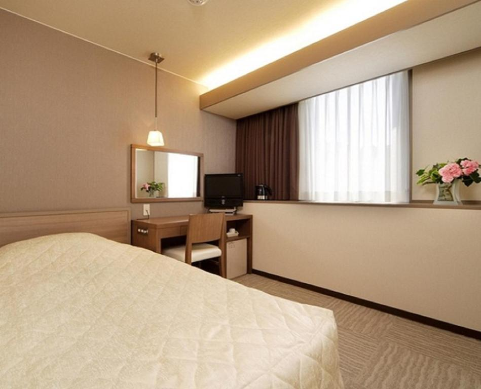 A bed or beds in a room at Niigata City Hotel