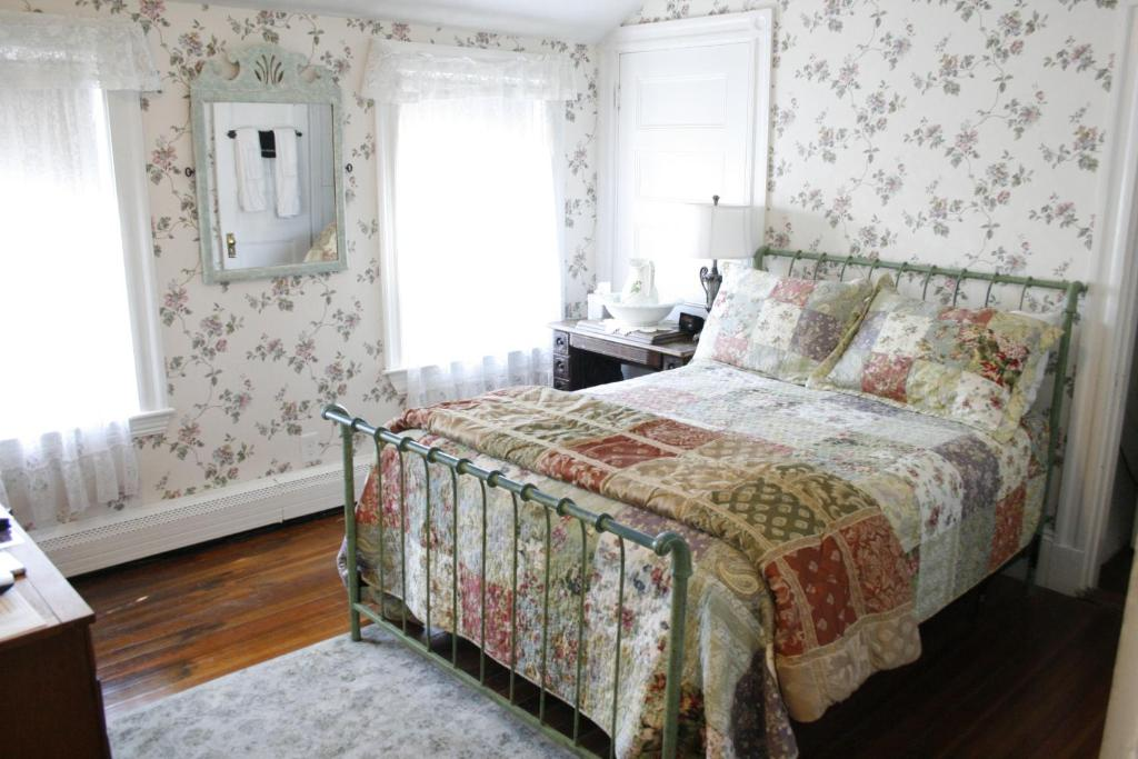 A bed or beds in a room at The Coolidge Corner Guest House: A Brookline Bed and Breakfast