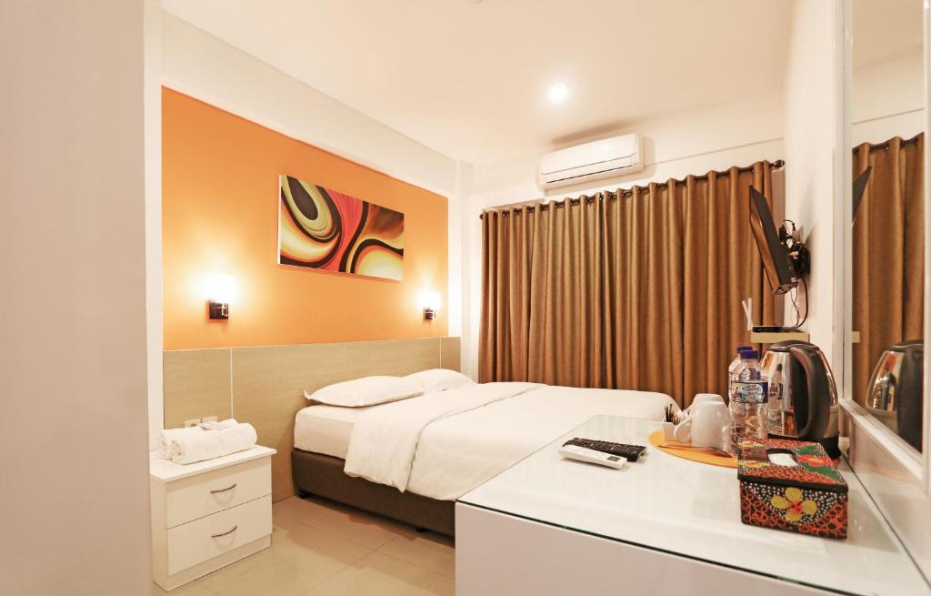 A bed or beds in a room at Fastrooms Bekasi Hotel