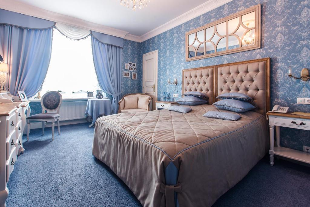 A bed or beds in a room at Russkiy Dvorik Boutique Hotel