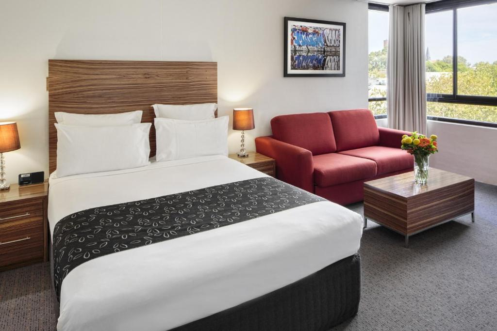 A bed or beds in a room at Cambridge Hotel Sydney