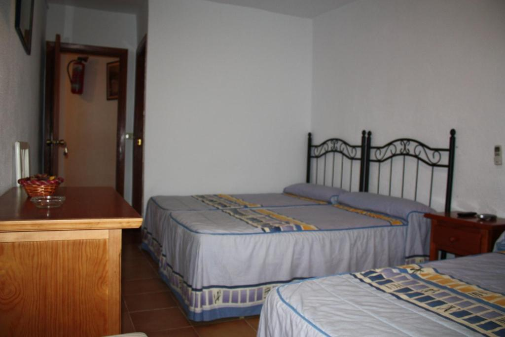 A bed or beds in a room at Hostal Tamarindos