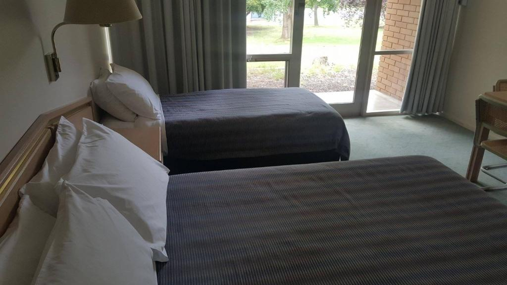 A bed or beds in a room at Moe Parklands Motel