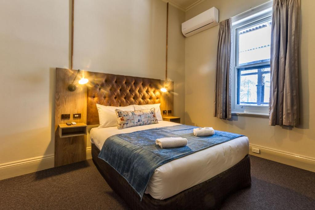 A bed or beds in a room at Pretoria Hotel
