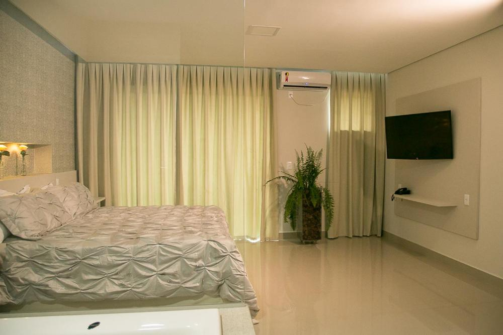 A bed or beds in a room at Peçanha Grande Hotel