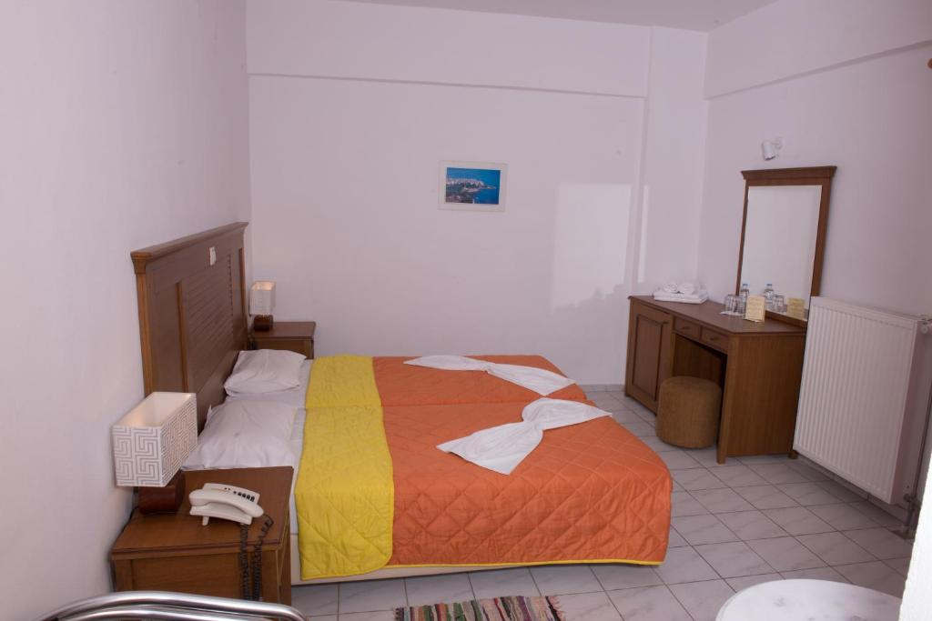 A bed or beds in a room at Alexander Beach Hotel