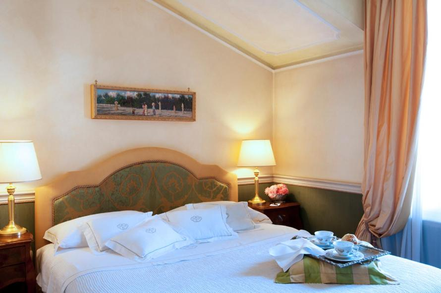 A bed or beds in a room at Petit Palais Hotel De Charme