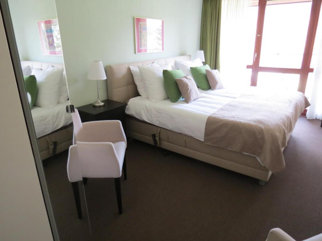 A bed or beds in a room at Hotel Residentie Slenaeken