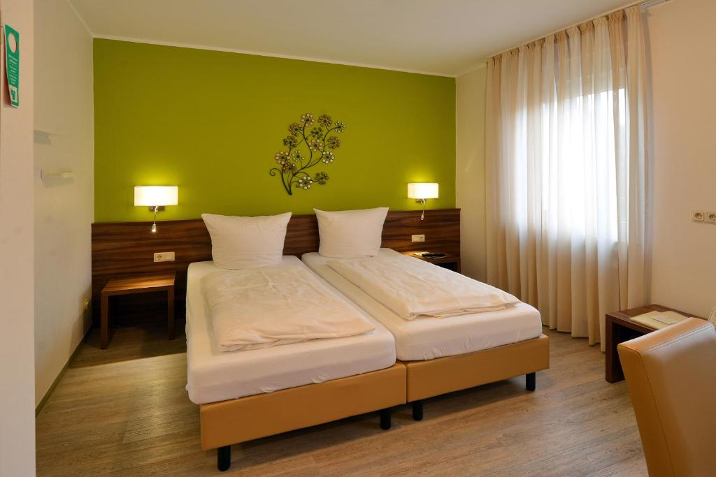 A bed or beds in a room at Keisers Hotel Garni