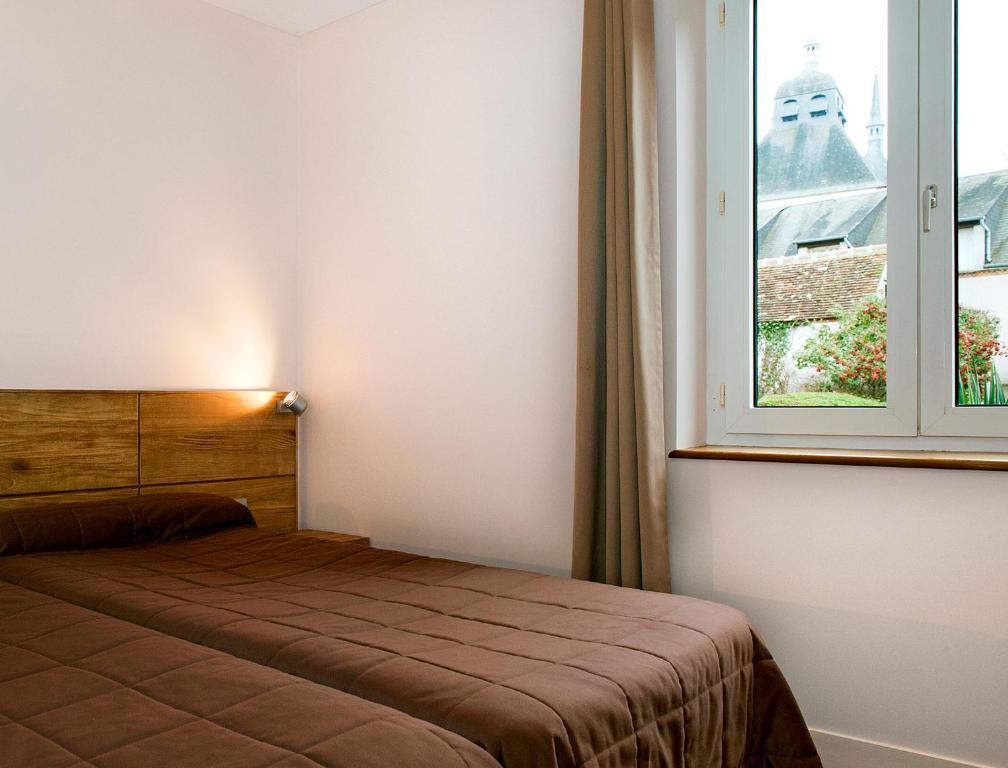 A bed or beds in a room at Hôtel Du Labrador
