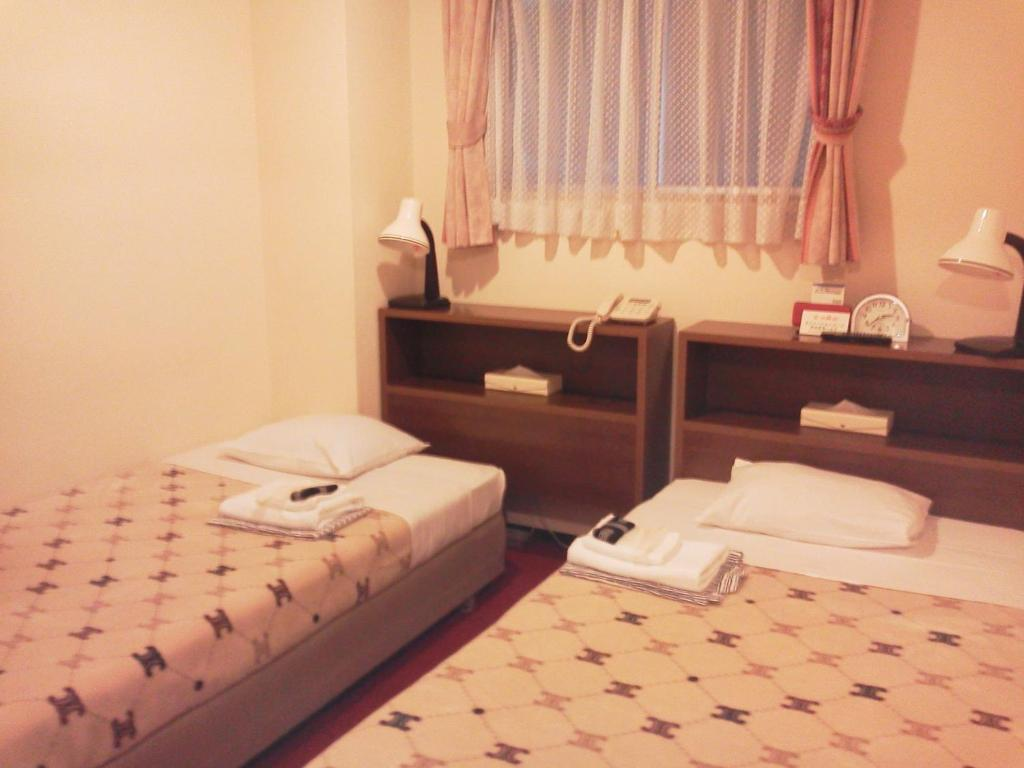 A bed or beds in a room at Hotel Yanagibashi