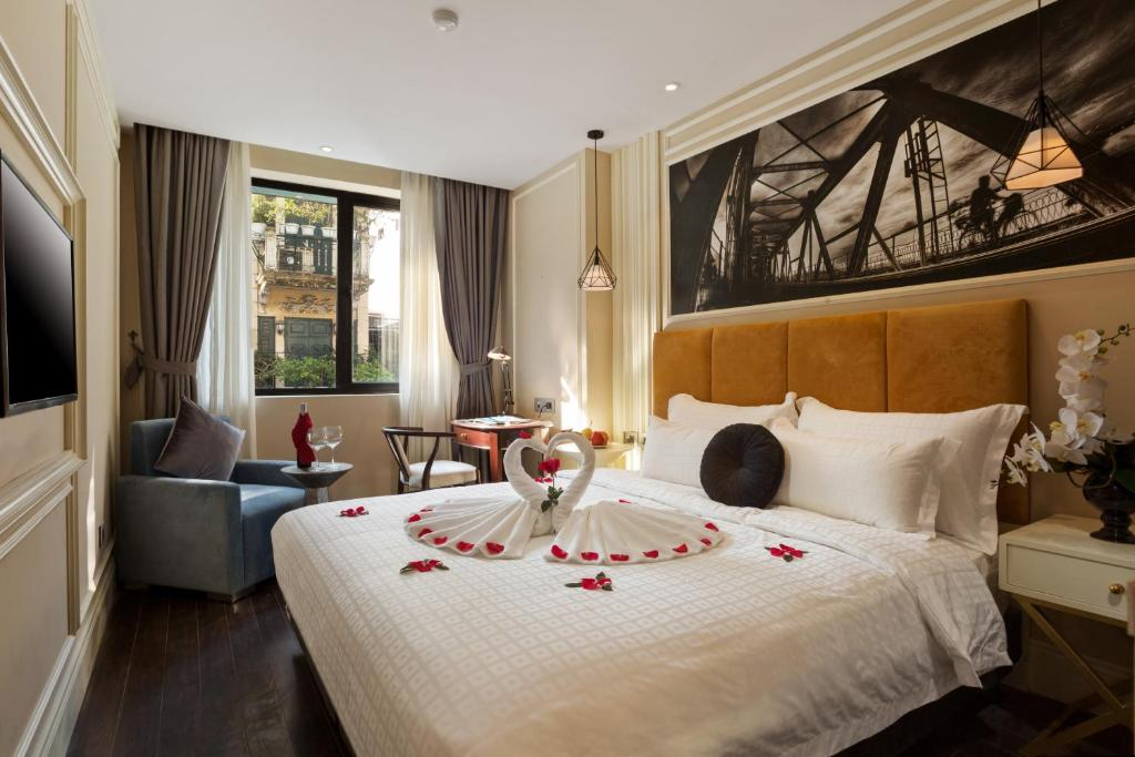 A bed or beds in a room at Hanoi La Storia Hotel