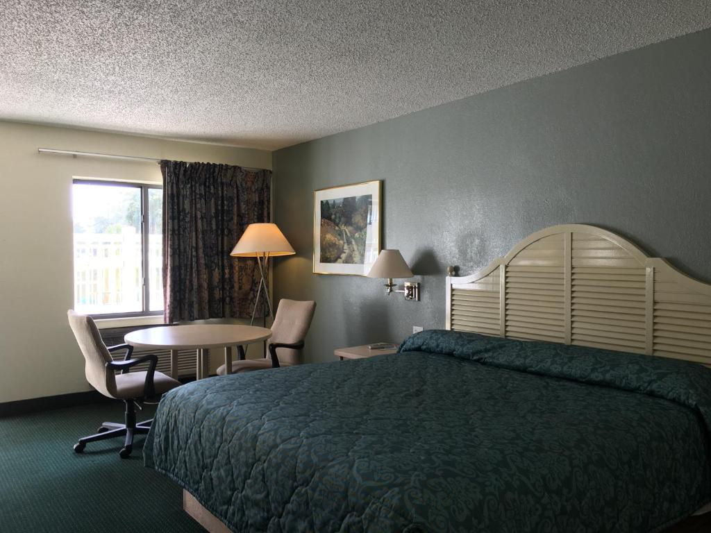 A bed or beds in a room at Riviera Motel