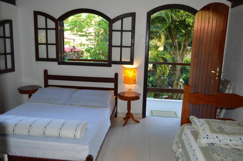 A bed or beds in a room at Pousada Recanto das Flores