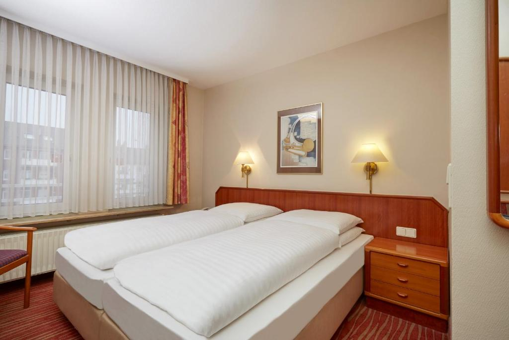 A bed or beds in a room at Novum Hotel Mannheim City