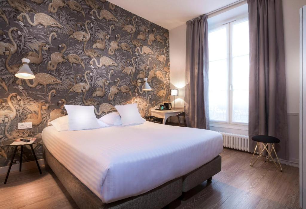 A bed or beds in a room at Hôtel Jeanne d'Arc Le Marais