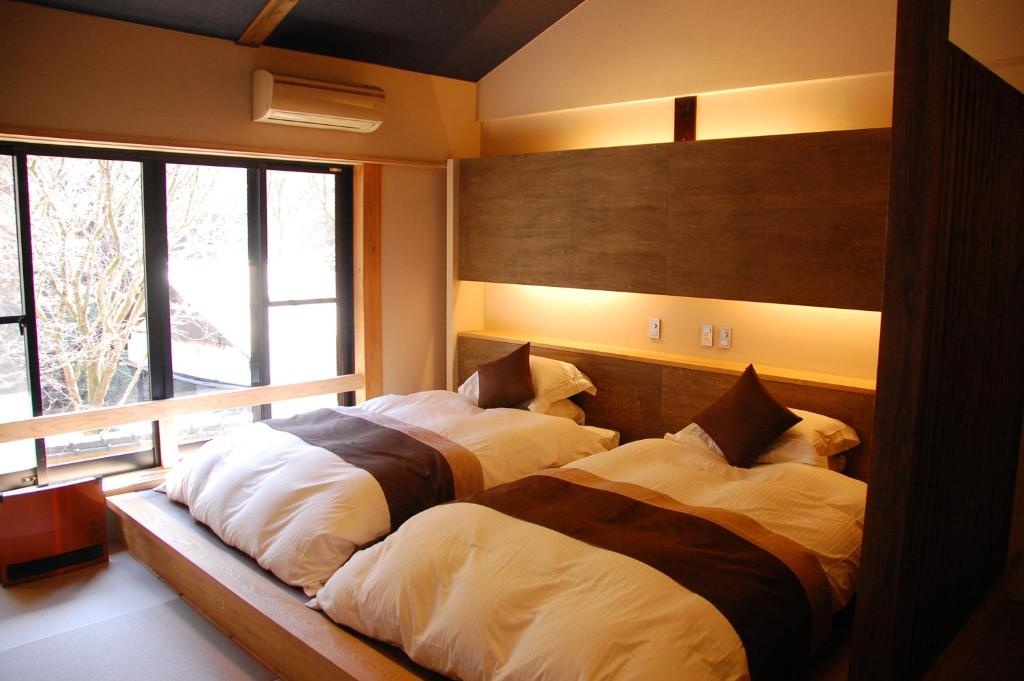 A bed or beds in a room at Ryokan Fujimoto