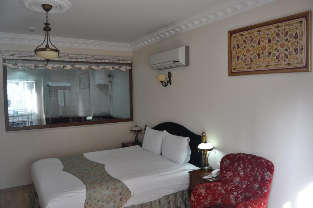 A bed or beds in a room at Basileus Hotel
