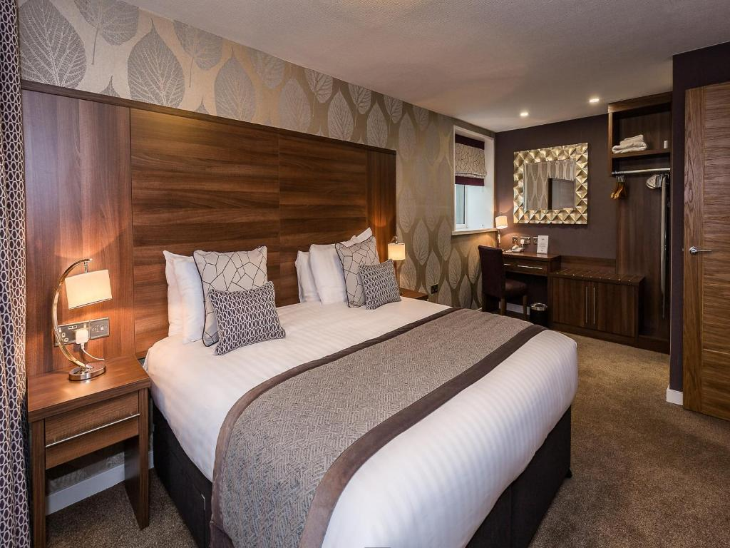 A bed or beds in a room at The Melbreak Country Hotel