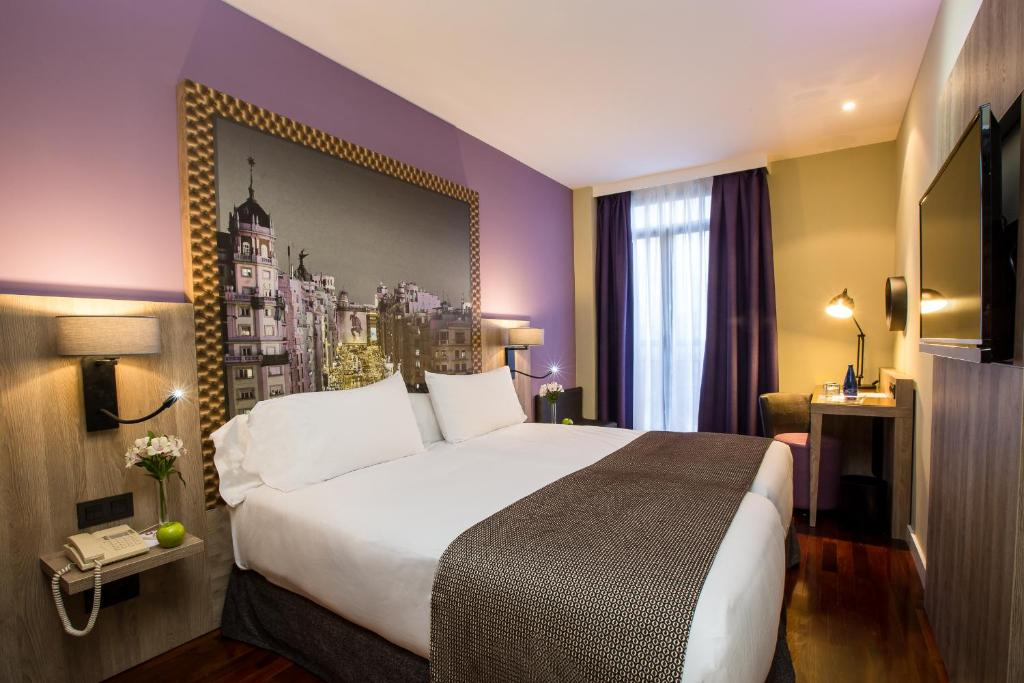 A bed or beds in a room at Leonardo Hotel Madrid City Center