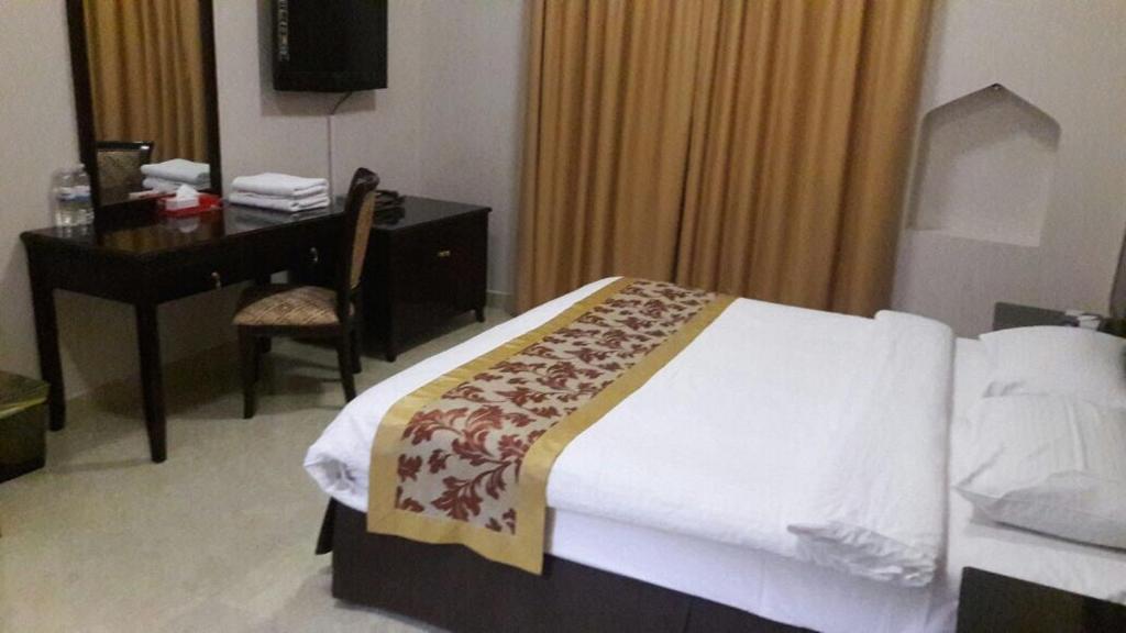 سرير أو أسرّة في غرفة في تاج الخليج للشقق الفندقية