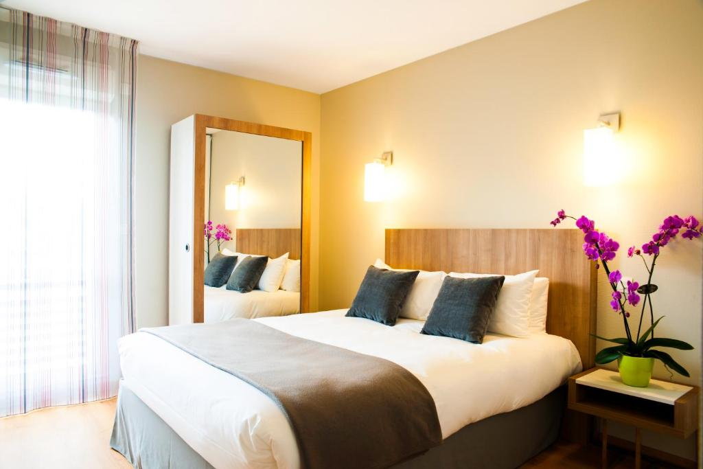 A bed or beds in a room at Lagrange Aparthotel Toulouse Saint-Michel