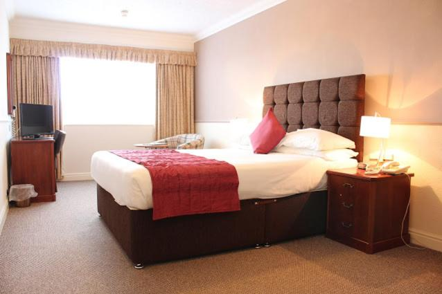A bed or beds in a room at The Crofters Hotel