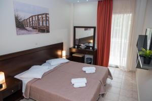 A bed or beds in a room at Malenia Hotel