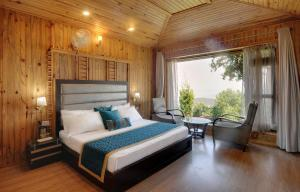 A bed or beds in a room at Ojaswi Himalayan Resort
